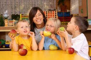teacher and three preschoolers having break for fruit